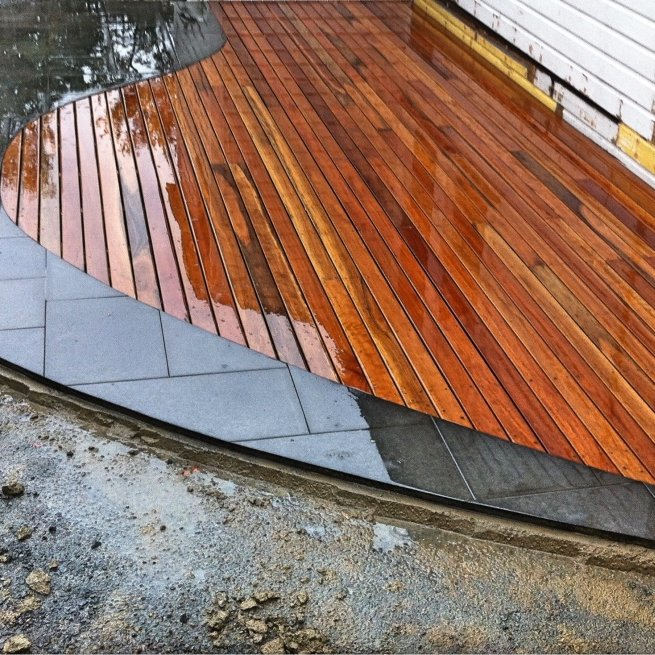 Curved spotted gum deck abutting curved bluestone paving
