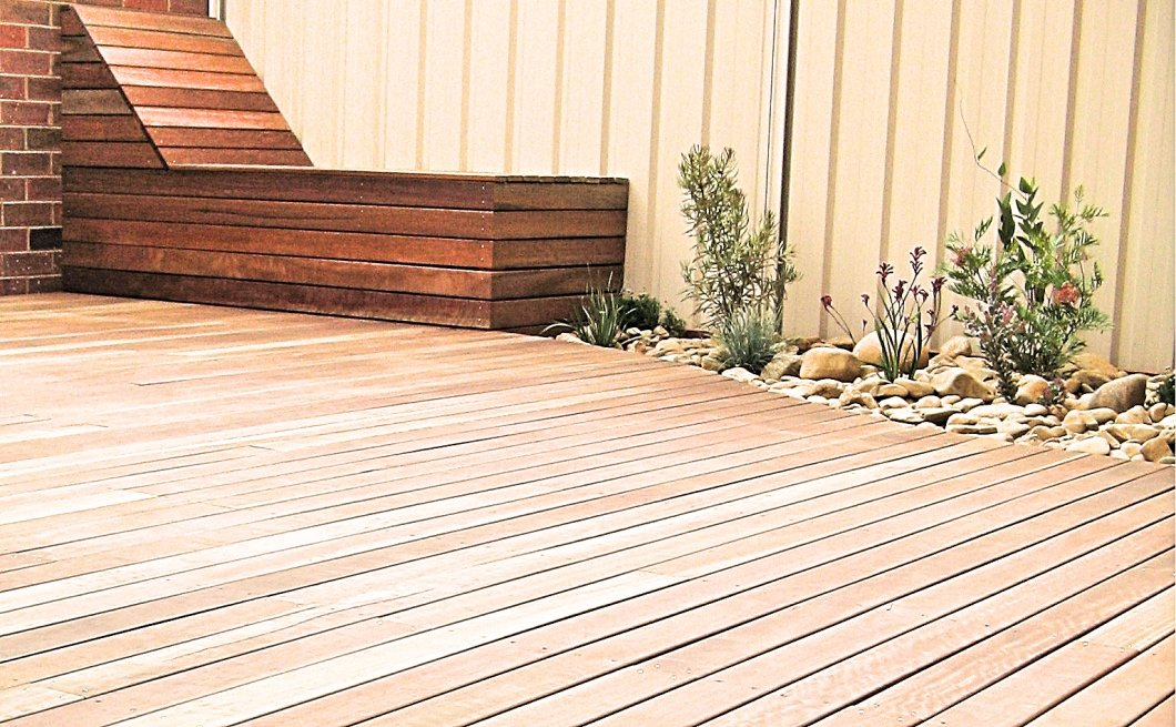 Spotted gum deck and day bed storage beside pebbled garden bed