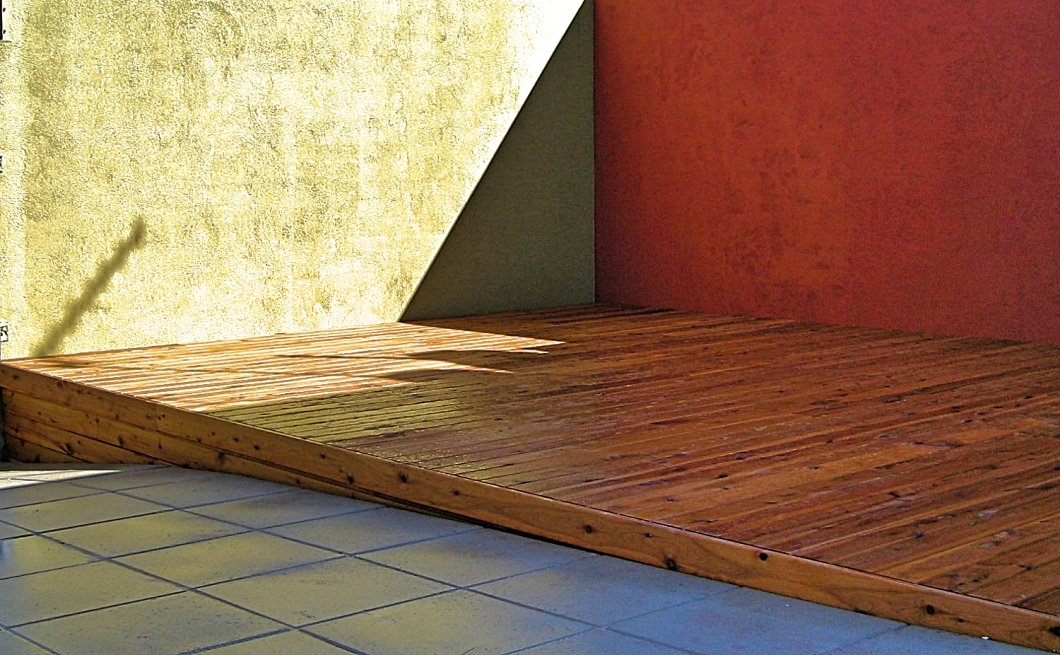 Native cypress (Callitris) deck between painted rendered brick walls and paving