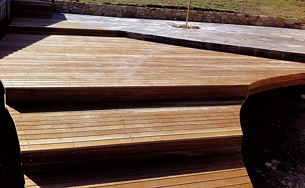 Spotted gum decking steps leading to black limestone paved patio
