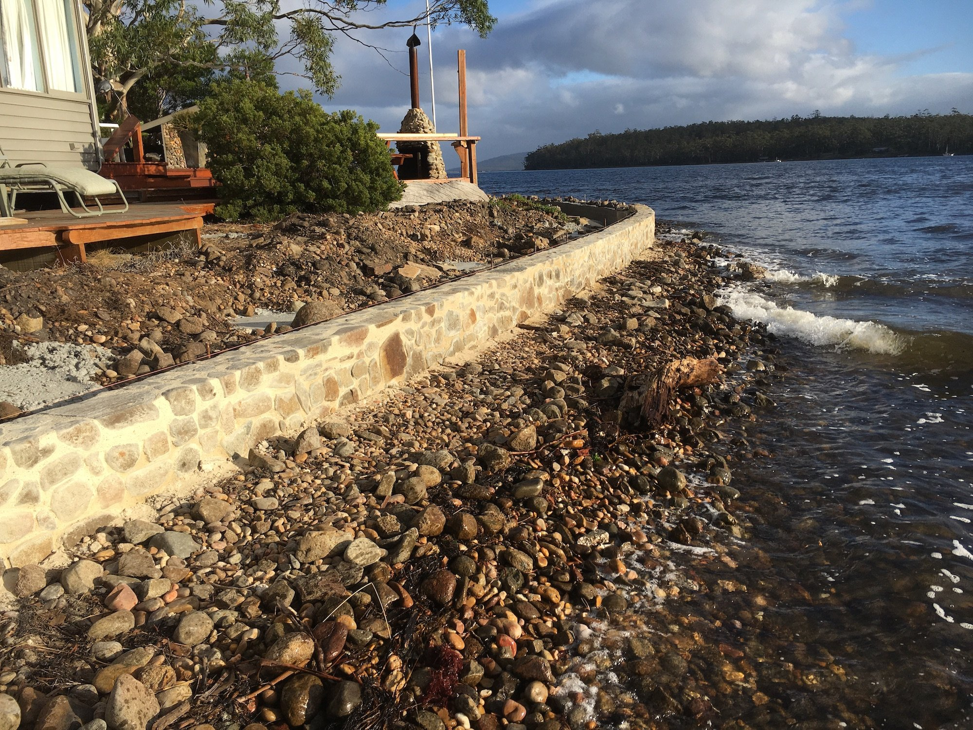 A reinstated sea wall, with pizza oven, outdoor and vegetation, with the backdrop of the Huon River.