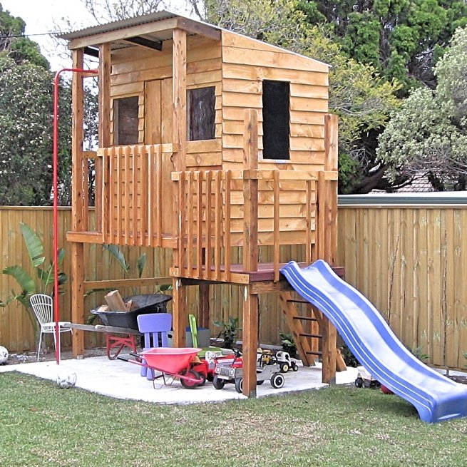 Timber cubby house on stilts with slippery slide and fire pole